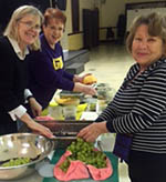 Brenda London, Leslie Capo and Ayse Brink prepare fresh fruit salad for the officers.